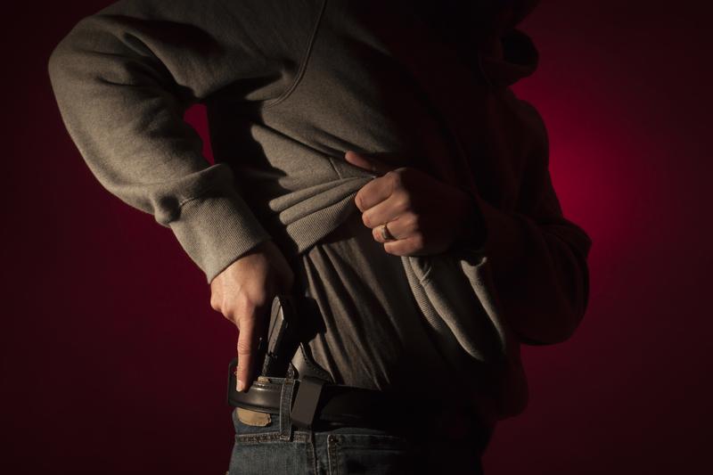 man drawing concealed handgun